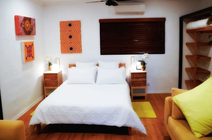 Spacious guest bedroom with comfortable Queen bed, quality bedding,  2 lounges,  local indigenous artwork, generous wardrobes & shelving, adjoining bathroom & an outlook to beautiful  established tropical gardens.