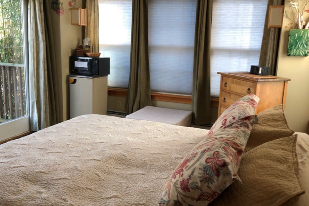 Queen bed with mini-fridge & microwave, chest of drawers with extra towels, & twin convertible ottoman.