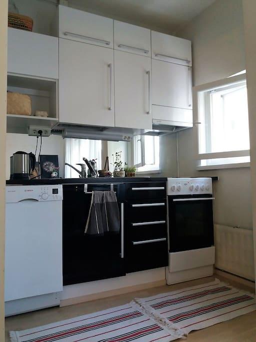 Small kitchen with fridge/freezer, stove, dish washing machine, kettle and Bialetti moccha maker.