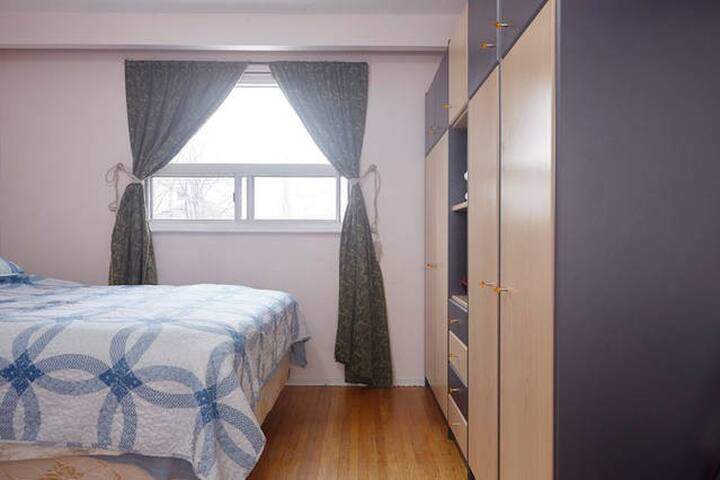A comfy Queen bed and a large bright window
