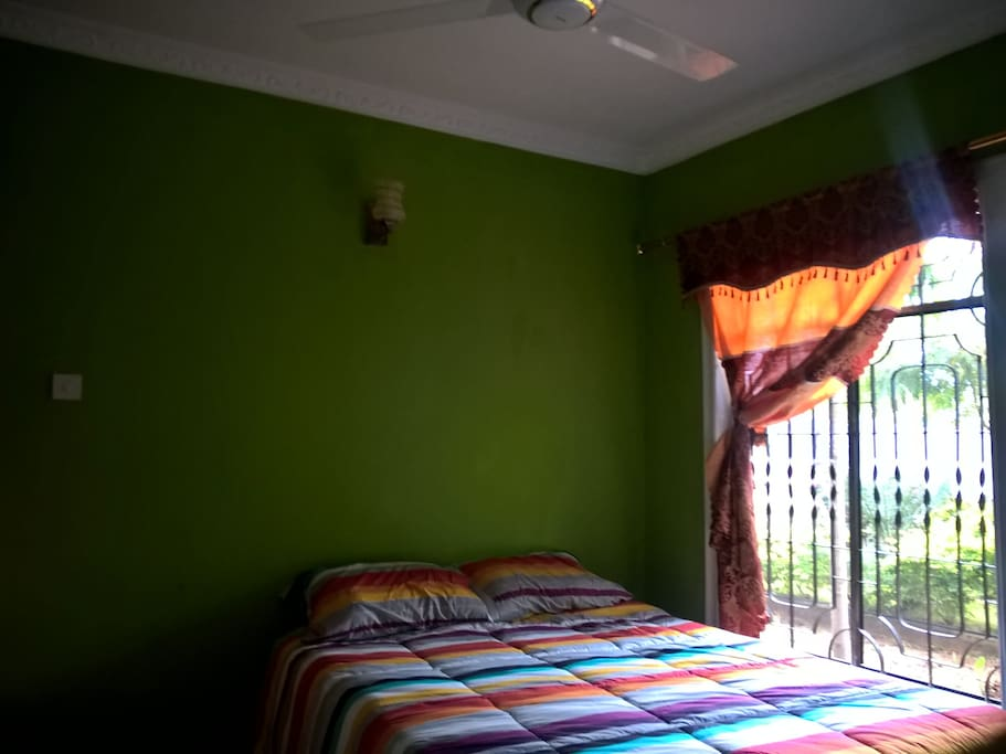 Bedroom with fan and garden view, mosquito screen