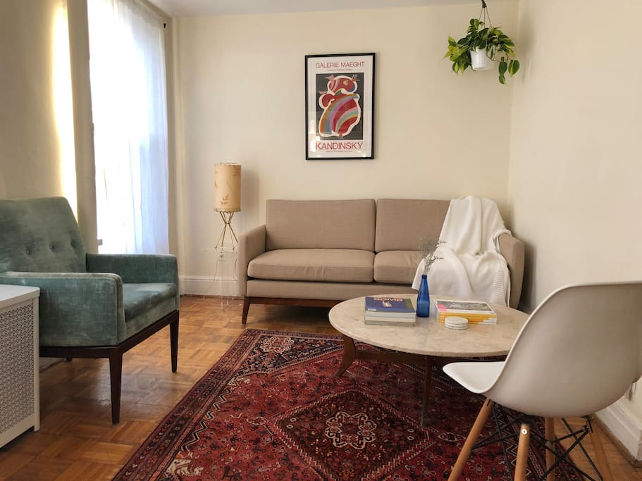 The other side of the living room: A cozy, mid-century modern seating area with marble coffee table and Persian rug.