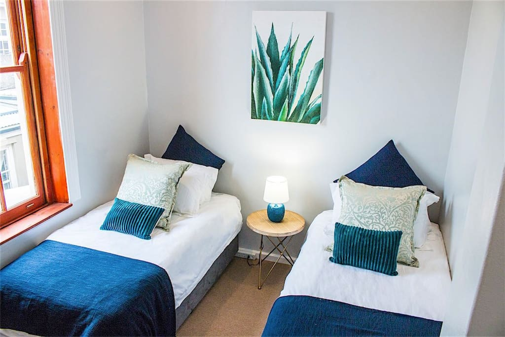 Guest bedroom with two single beds, comfortable mattresses, bedding and linen