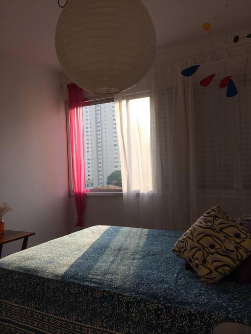 quarto com cama de casal, janelão e armário embutido