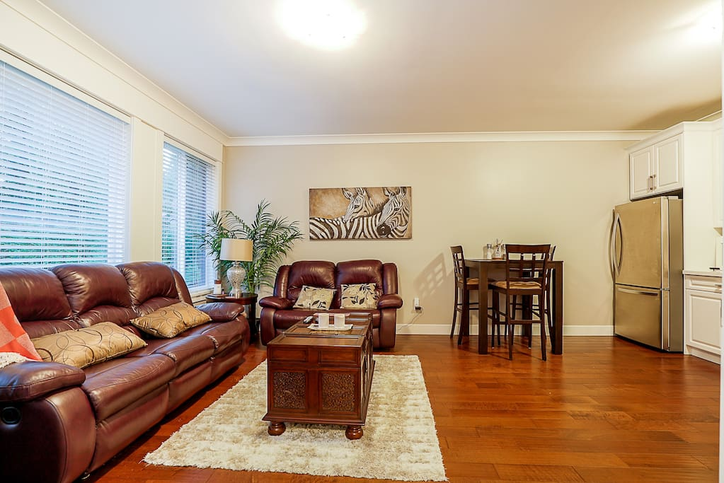 Living Room with reclining leather couches. Blankets and board games are in the coffee table/trunk