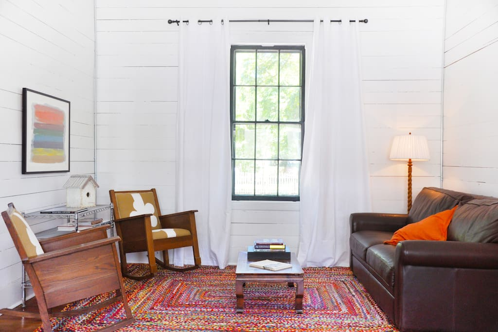 Living Room - 12 ft. ceilings with original shiplap walls and a queen sleeper sofa