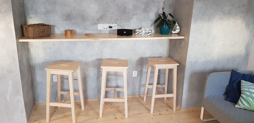 Posezení s barovými židličkami, dlouhá pracovní plocha pro Váš notebook či tablet s dostatkem elektrických zásuvek. V případě dlouhodobých pracovních pobytů můžeme po dohodě doplnit apartmán pracovním stolem.