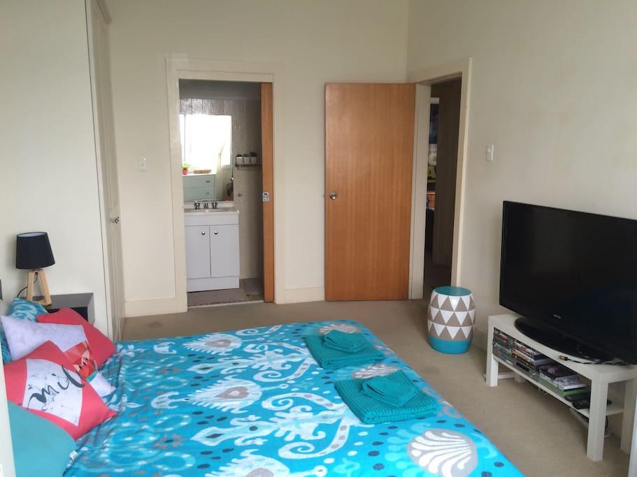 A view of the door to the ensuite bathroom (left) & bedroom door (right)