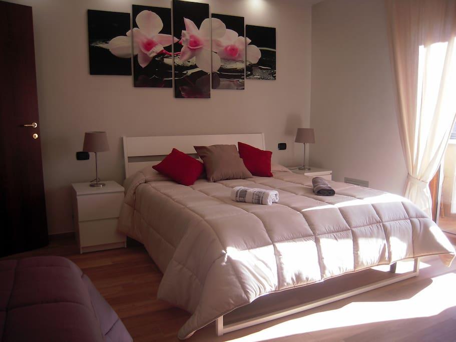 Camera con letto matrimoniale e letto singolo. Accesso al balcone