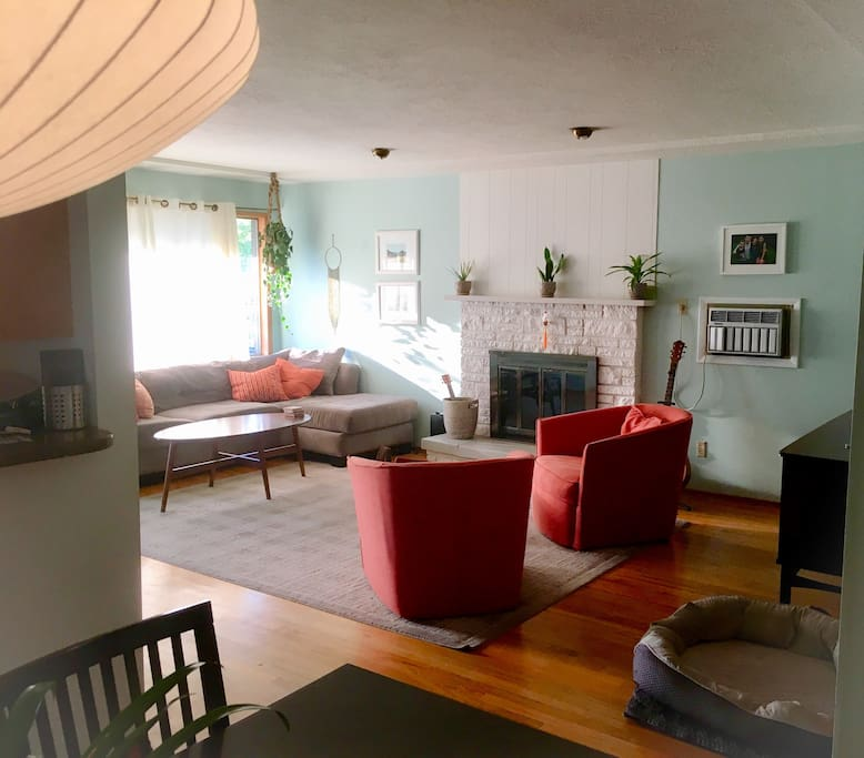 Living area is a great space for conversation or relaxation, with comfy couch, swivel chairs, large smart TV, wii, and air conditioner wall unit.