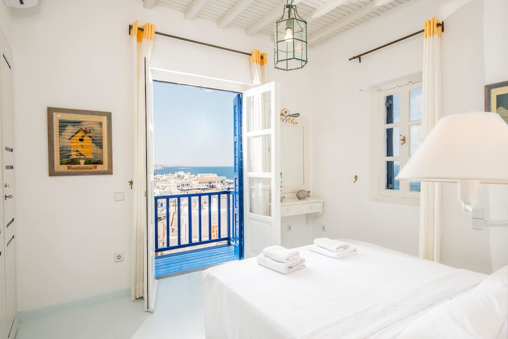 The first bedroom with spectacular views to the town of Mykonos, Delos island and the sunset