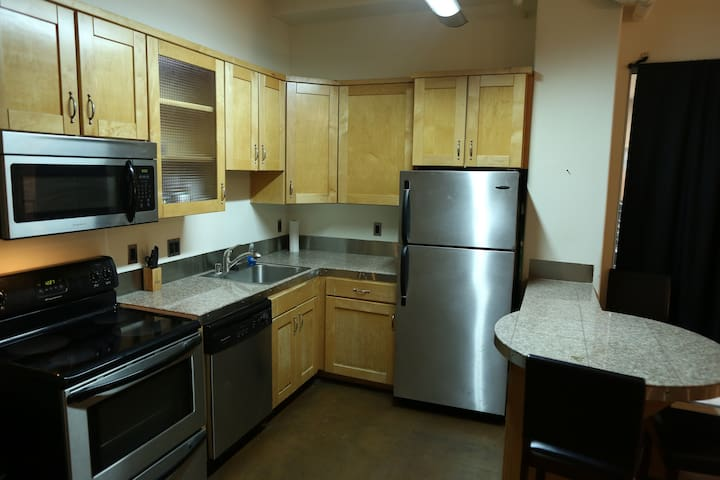 Fully stocked kitchen with pots, pans, plates, cups, & napkins. Stove/oven, microwave, dishwasher, garage disposal & fridge.