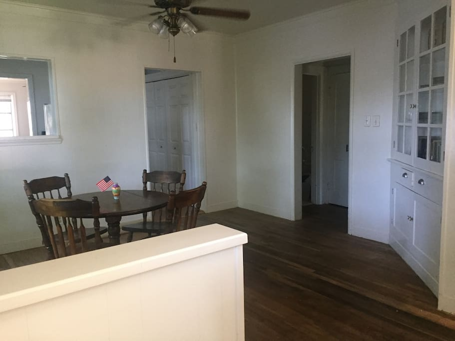 The dining room, access to the hallway leading to three bedrooms and bathroom, as well as entry to kitchen, back utility room and back door to deck.  Note: this photo shows dark wood floors before they were white-washed this summer.