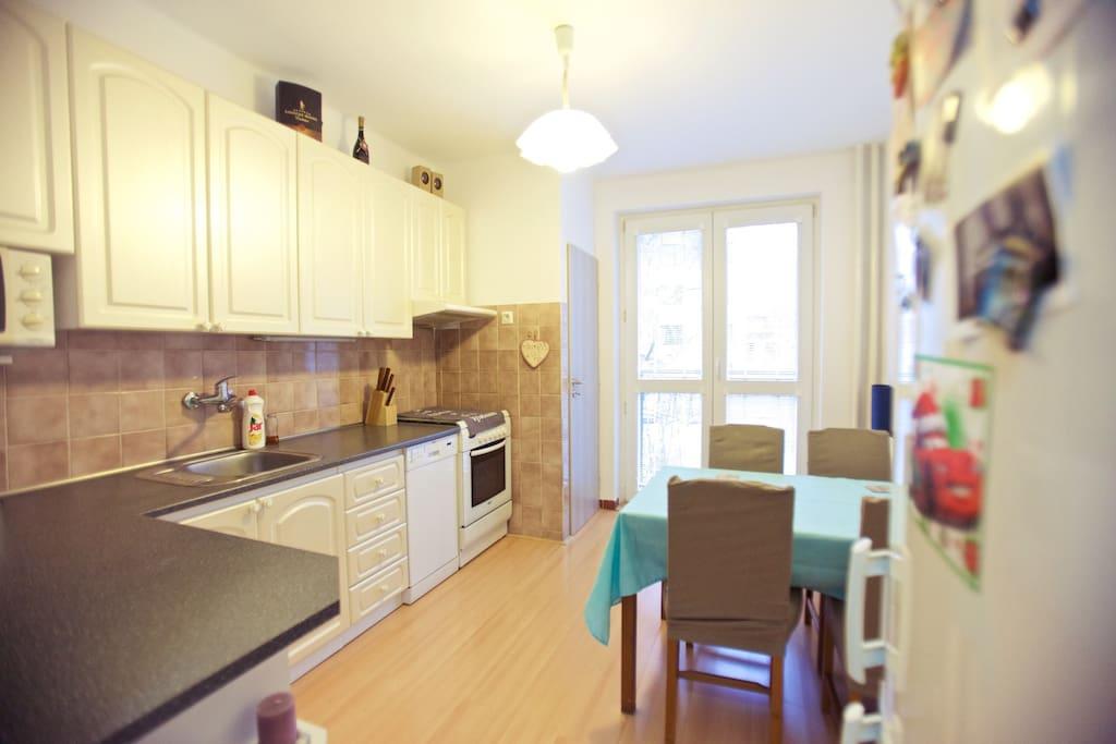 Kitchen with 4 seating, stove, fridge, balcony