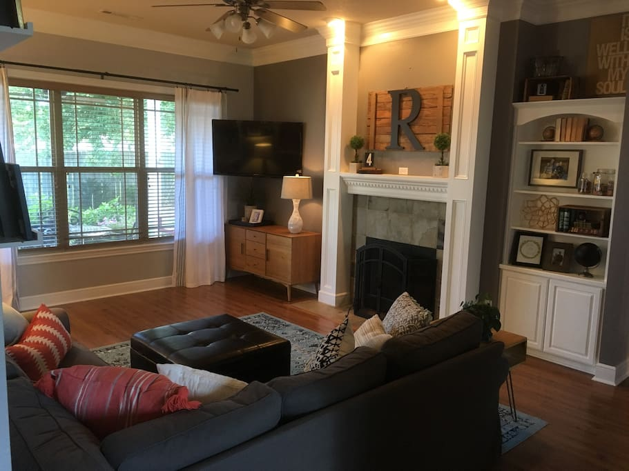 """Living room with large sectional and 50"""" TV, Apple TV, and blueray."""