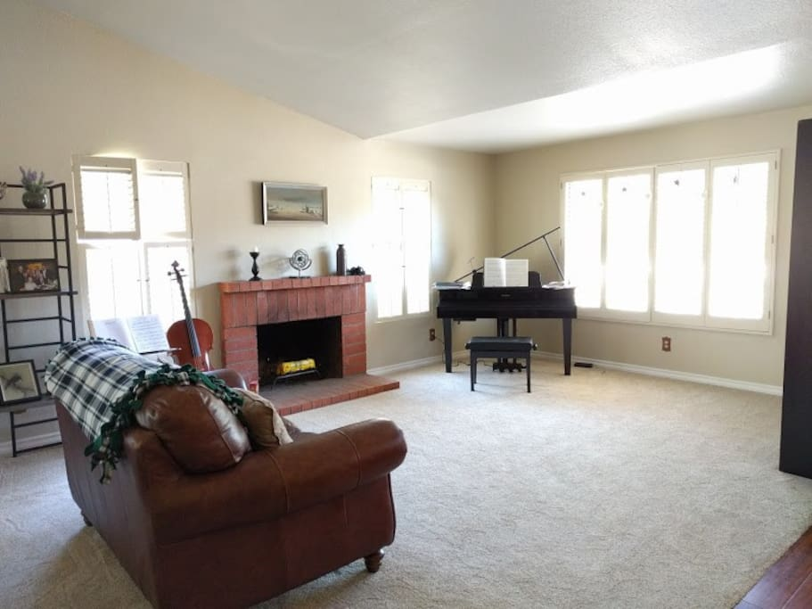 """Spacious living room with an electric """"grand"""" piano.  Again, we have added a rocking chair for more seating."""