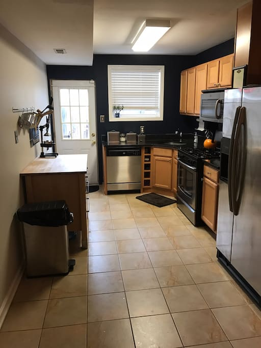 Kitchen equipped with dishwasher, coffee maker, water maker in refrigerator and patio access.