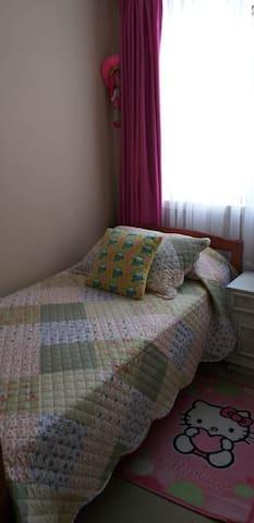Dormitorio con cama de una plaza y velador