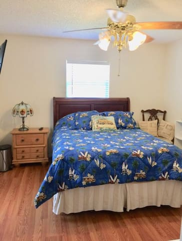 Guest room with queen bed, TV, dresser, large closet and outdoor access.