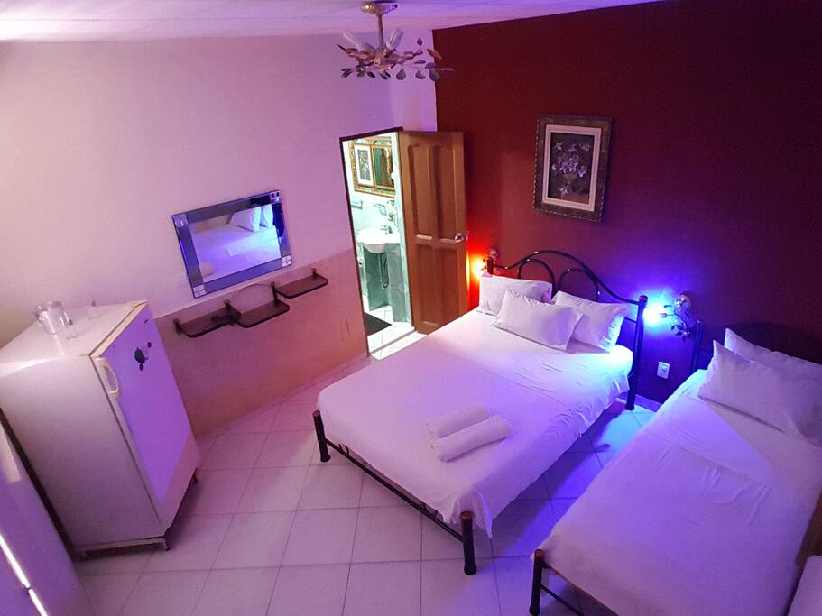 Un cuarto con cama camera y una individual, con servicio de minibar, acondicionador, TV, Ventilador y servicio de limpieza a la habitación diario.