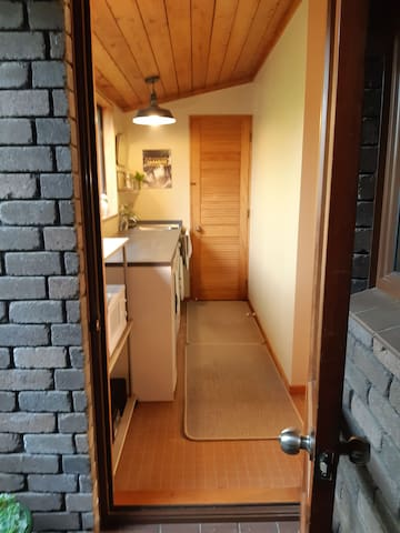 Entrance door leading into combined kitchenette and laundry room of Apartment