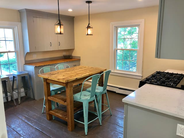 Eat-in rustic kitchen with 6 burner gas stove.