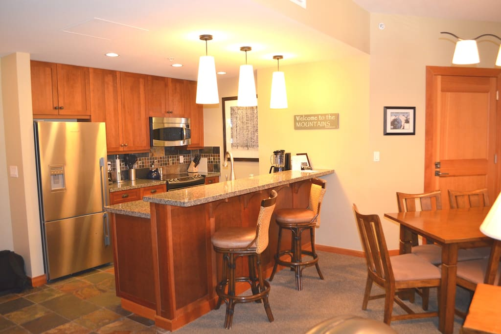 Fully Equipped gourmet kitchen with stainless steel appliances and large granite island with two bar chairs.