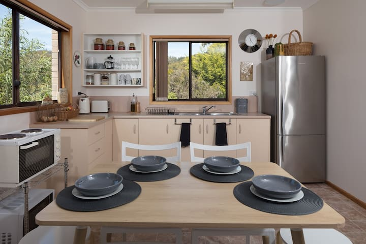 Bright inviting kitchen with all that you need including fridge over hot plates and microwave.