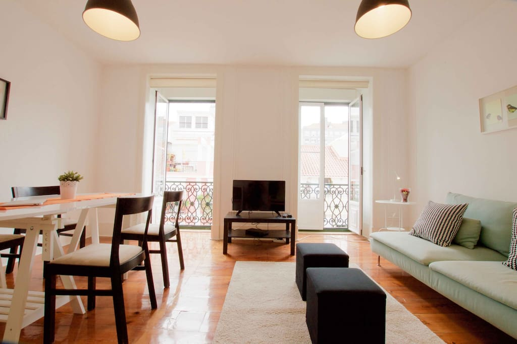 View of spacious living and dining area with plenty of natural light. High ceilings and long wood floors, typical of Lisbon architecture.