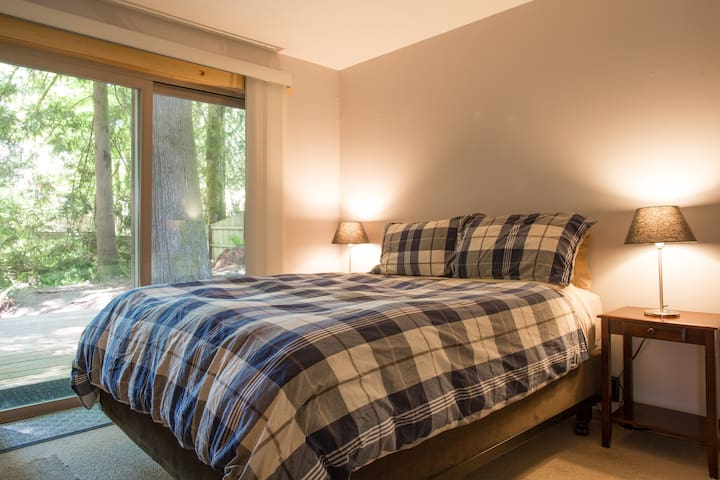 Queen bedroom opens up to a wooded patio.