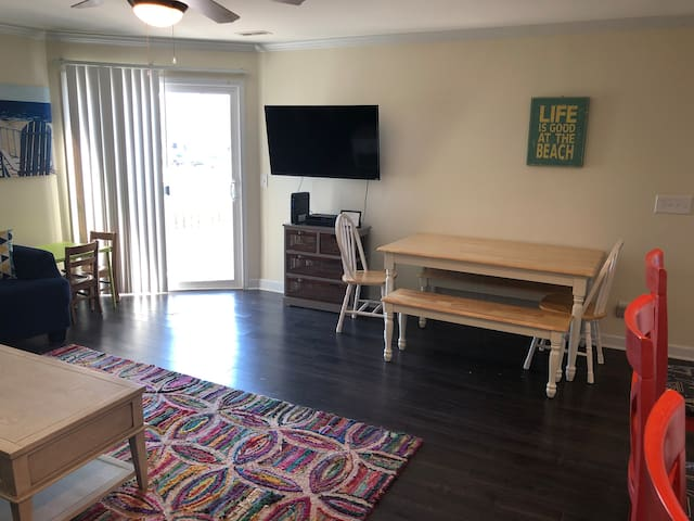 Large flat screen TV with tons of channels for your entertainment, along with a spacious dining table and entry to the balcony!