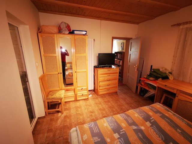източната спалня с гардероба и шкафа с телевизора, масичка за багаж, бюро и стол