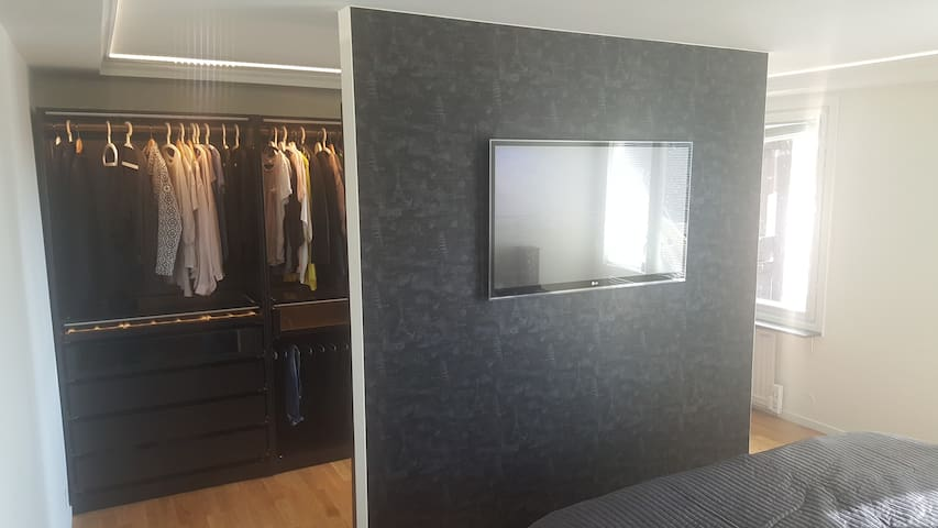 Master bedroom with walkin closet and TV.