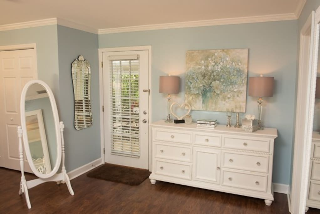 Dresser with full length mirror and door leading to patio