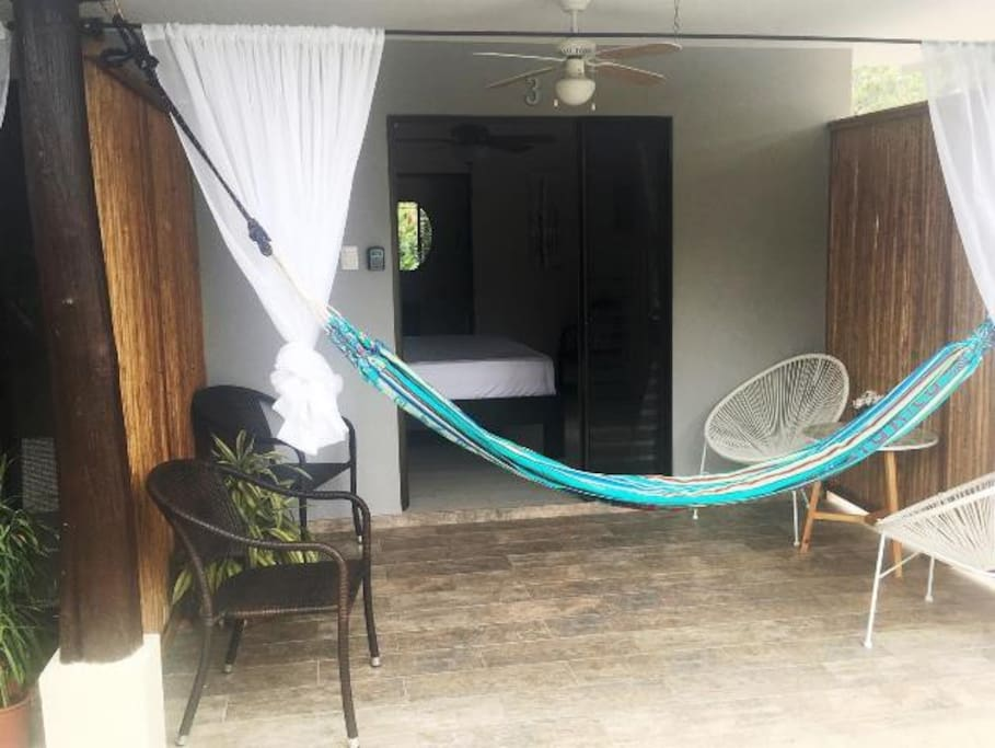 Private porch area with hammock and curtains
