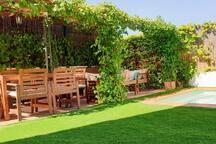 Piscina y jardín exterior con zona de estar.