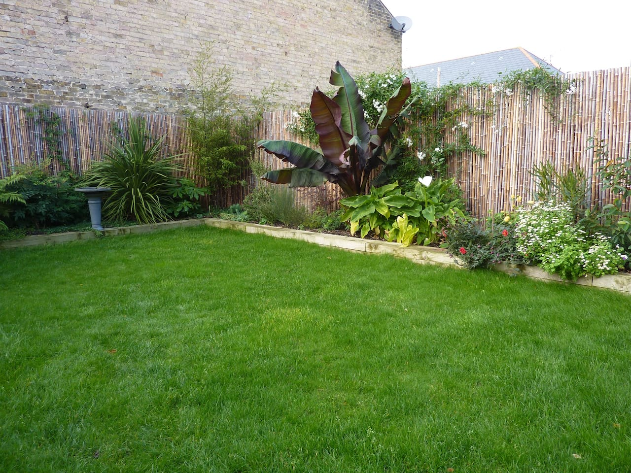 Luscious tropical enclosed private garden with Webber BBQ, patio, seating/sofa & chiminea