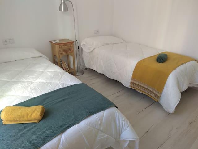 dormitorio con 2 camas individuales, aire acondicionado, calefacción,  y estantería .