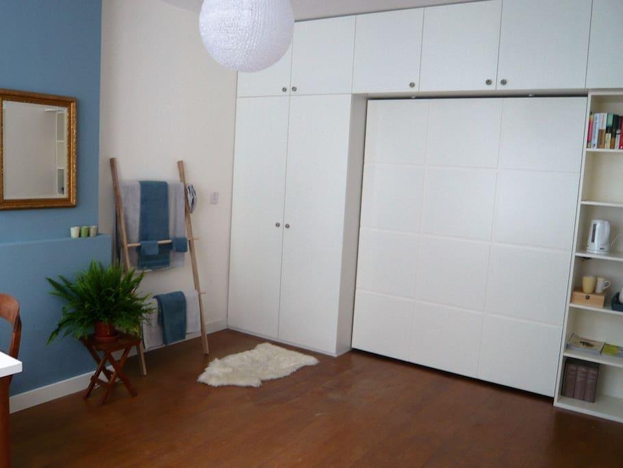 Grote, houten wandkast met veel opbergplekken en ruimte om het bed in te klappen.