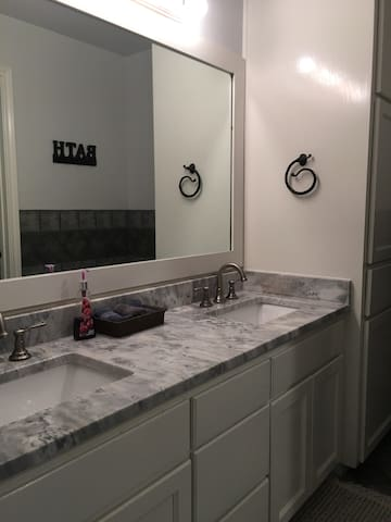 The bathroom has a two sink area that are separated from the toilet/shower/tub space by a door.    This toilet space may be a shared space, but three other bathrooms are available in other parts of the house that can be used.