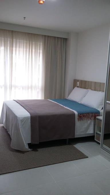 Flat - suíte com cama queen em colchão resistente e aconchegante, cortina e black out. Travesseiros adicionais - se preciso.