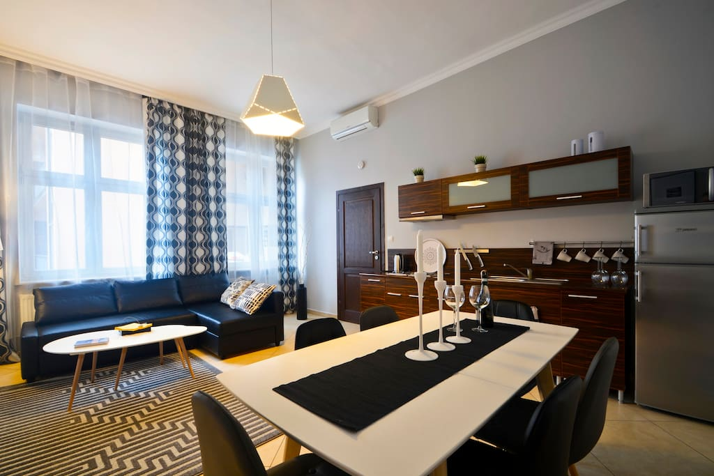 Room in apartment with kitchenette, dining table, sofa-bed, TV
