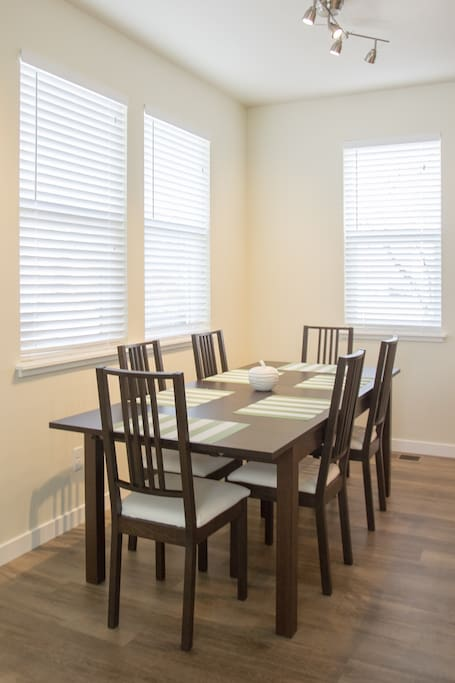 The dining room has many windows for natural daylight as well as a modern lamp to offer plenty of light in the evening. Enjoy your family dinner here with seating up to 10!