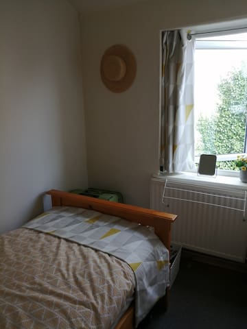 Lovely sunny single bedroom, with a comfortable bed and bedside table, lamp & storage.