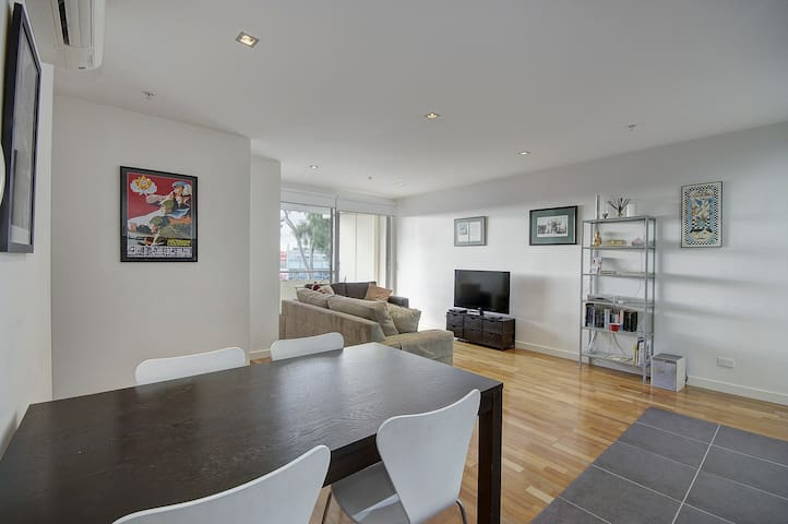 A Dining table for 4 or 5 people open to the lounge are with wall mount TV