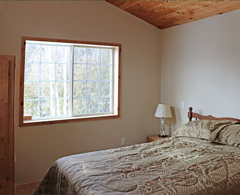 Garden view guest bedroom with private entrance and shared bathroom on main floor
