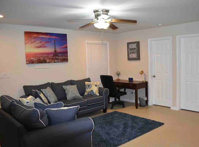 Living room featuring a sofa-bed, a desk, wall mounted flat screen smart TV, recessed light, ceiling fan