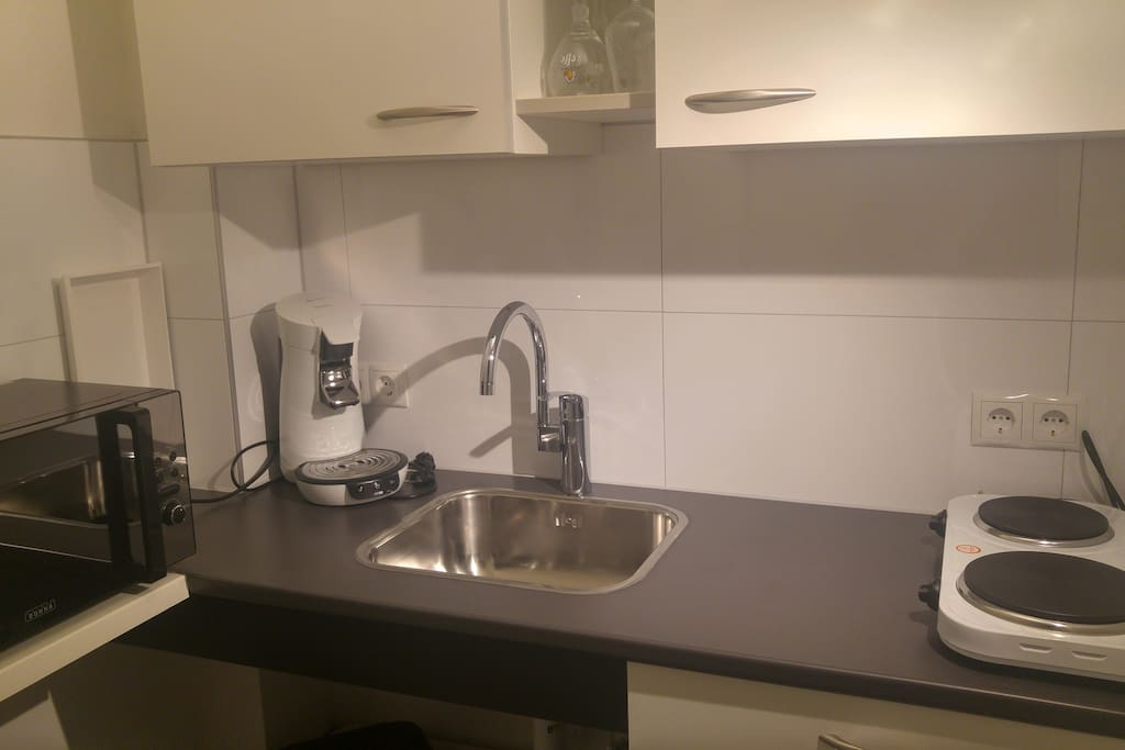 Een keukentje met voorzieningen om een kopje koffie te zetten , een koelkastje   kook plaatje borden bestek waterkoker wasbak, etc