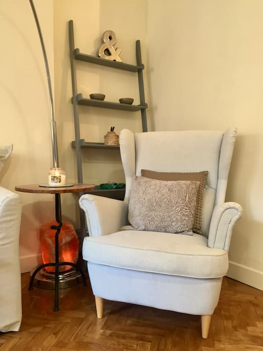 Living room corner with comfortable armchair, Himalayan salt lamp and ladder shelves with decor