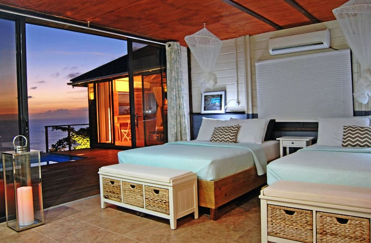 Spacious main bedroom with two queensize beds, private en suite, A/C and an oversized baywindow for sunsets...